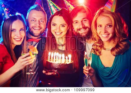 Joyful friends with birthday cake cheering in night club
