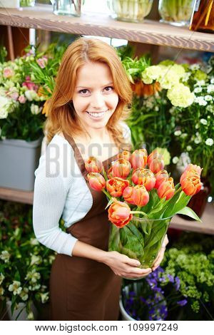 Young florist with fresh red tulips looking at camera