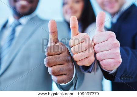 Close-up of business group keeping thumbs up