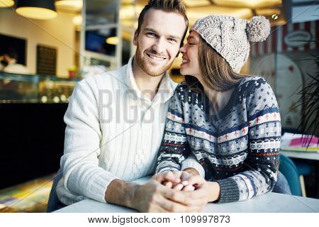 Affectionate dates sitting in cafe