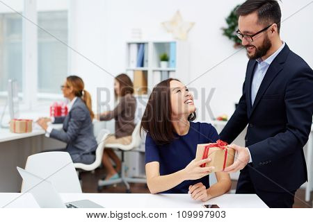Handsome businessman making Christmas surprise to his secretary in office