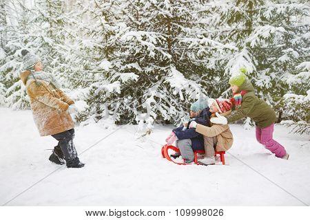 Little friends riding on sledge in winter park