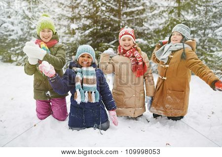 Cute little friends playing snowballs in winter park