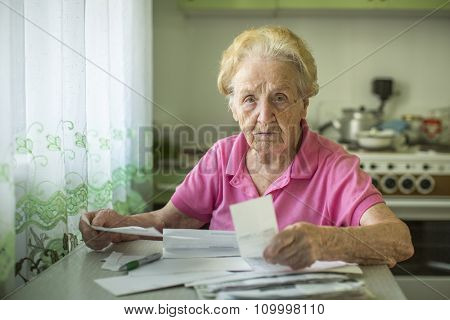 An elderly woman writes of account for the payment of utilities.