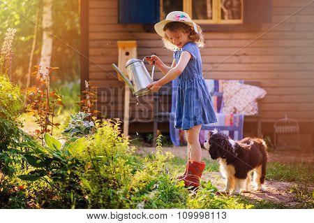 child girl watering flowers with her dog in summer garden, little helpers, outdoor activities on vac