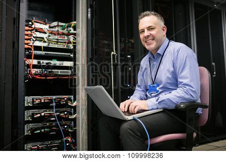 Technician using laptop in server room at the data centre