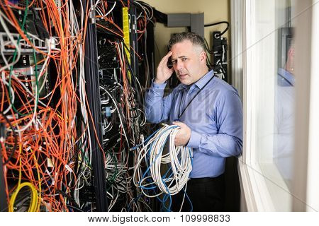 Stressed technician looking at open server locker at the data centre