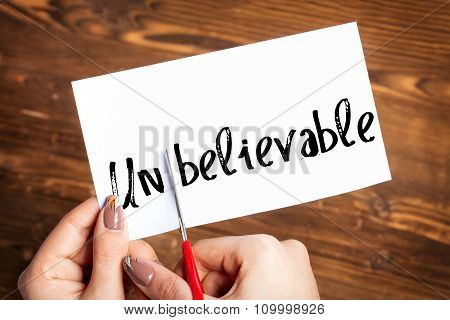 Woman hands cutting card with the word unbelievable