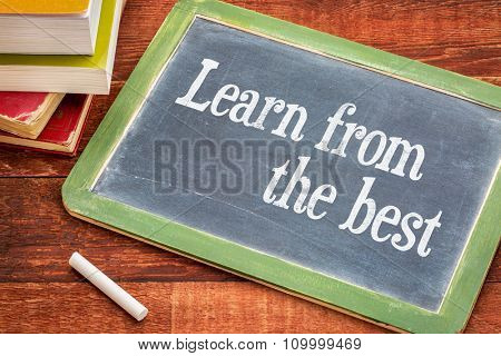 Learn from the best advice - white chalk text on a slate blackboard with a stack of books against rustic wooden table