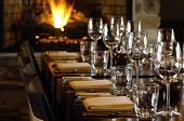 foto of restaurant  - a long table is set at a restaurant by the fire - JPG