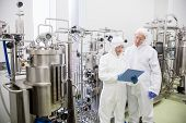 Scientists working with large vat in the lab poster
