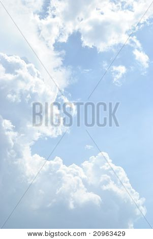 Blue sky with cumulus clouds in contrary light