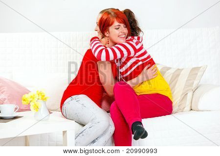 Two cute young girlfriends sitting on sofa and happily embracing
