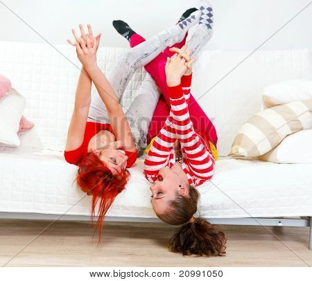 Funny young girlfriends in playful mood lying on sofa with legs raised up