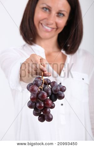 35 years old woman giving a red grape
