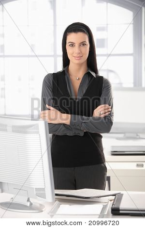 Portrait of smart office girl standing at desk with arms folded, smiling.?