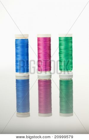 Colorful spools of thread on a table against a white background