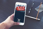 Black Friday Sale Tag With Shopping Cart On Mobile Screen,hand Holding Smart Phone Over Black Book A poster