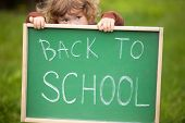 Cute Toddler Girl Hiding Behind A Back To School Blackboard poster