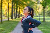 Woman Holding Painful Back In Park poster