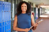 Middle aged black female teacher smiling in school corridor poster