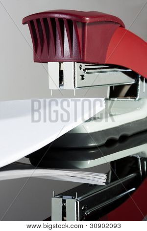 A classic red office stapler with documents