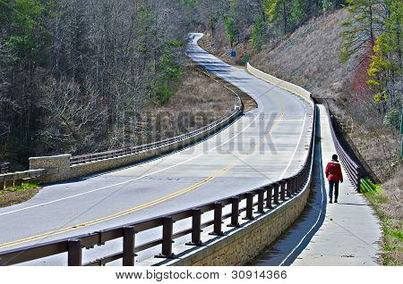 Camino sinuoso y mujer caminando