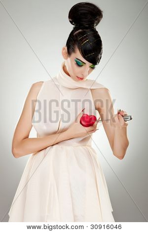 brokenhearted woman in fashion dress pointing a big kitchen knife at her heart