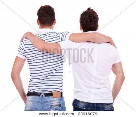 Hintere Ansicht von zwei Freunden Stand nimmt und sah etwas auf weißem Hintergrund