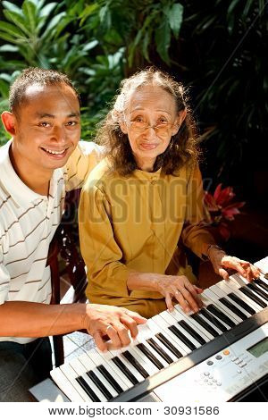 Ethnic Senior Woman And Adult Man Playing Piano