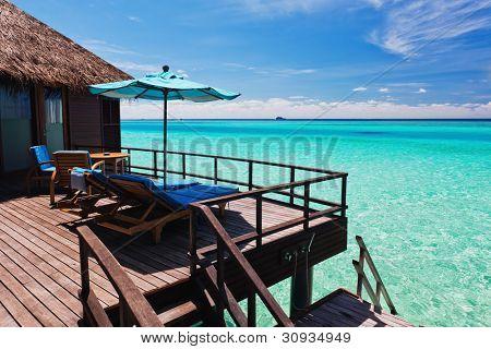 Overwater villa balcony overlooking green tropical lagoon