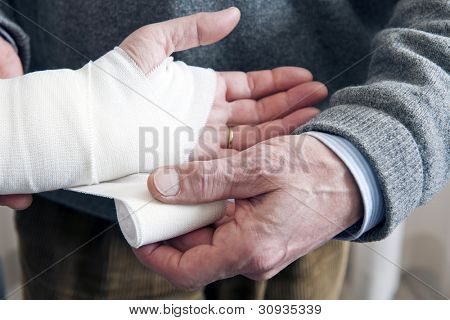 Doctor, bandaging a strained wrist of a patient with a swathing band
