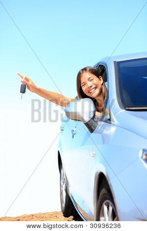 Car woman showing keys excited, happy and joyful. Young woman driver smiling in her new car. Mixed race Asian / Caucasian female model above the clouds on beautiful summer day.