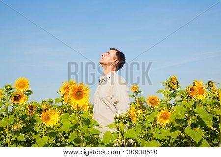 older man enjoying breathing deep in parc field
