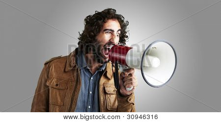portrait of a young man shouting with a megaphone against a grey background