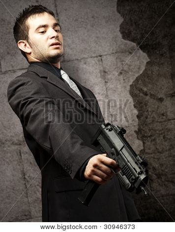 mafia man aiming down with a gun against a vintage wall