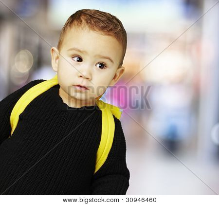portrait of a boy with his yellow backpack against a street background