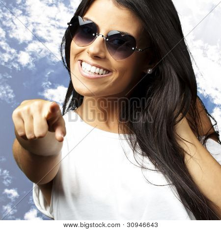 portrait of a young woman wearing heart sunglasses pointing against a blue sky background