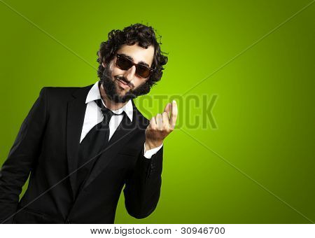 portrait of a young business man gesturing money over a green background