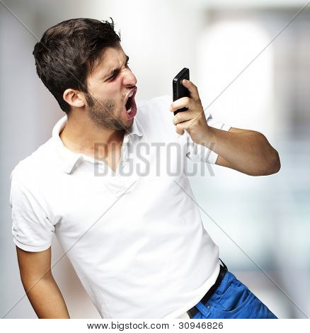 portrait of a young man shouting at a mobile, indoor