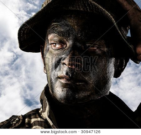 portrait of a young soldier painted with jungle camouflage against a blue sky background