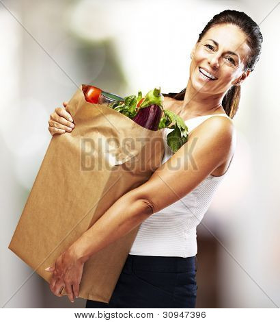 portrait of a middle aged woman smiling and carrying the purchase indoor