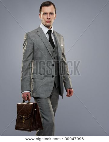 Businessman with a briefcase isolated on grey.