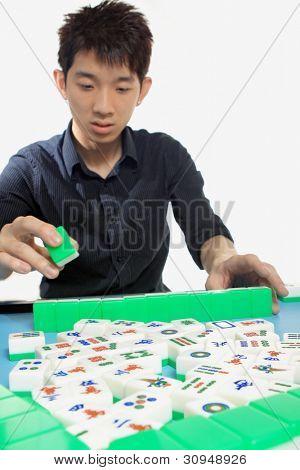 Chinese man play Mahjong, traditional China gamble.