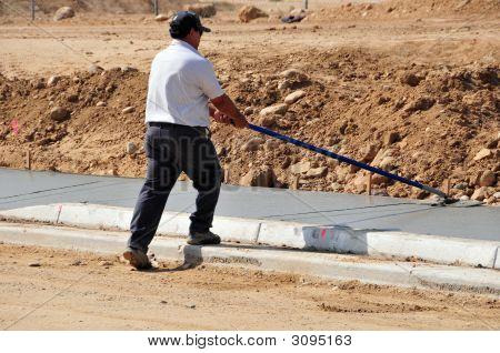 Workman Finishes Concrete Sidewalk