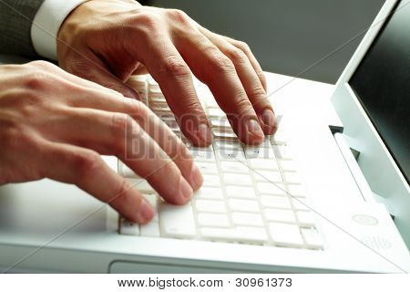 Close-up of male hands over white keyboard of laptop during typing