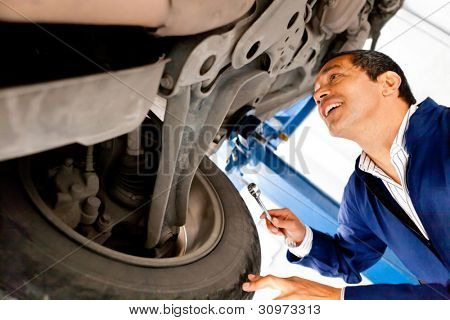 Mechanic working under a car at a repair shop