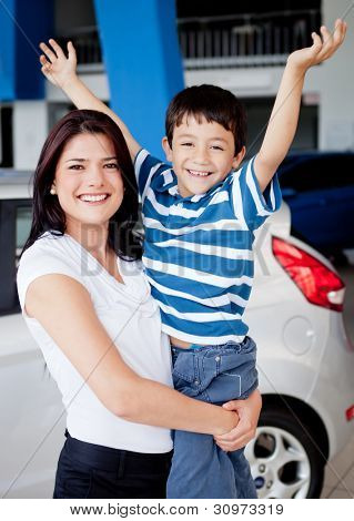Happy mother and son buying a car