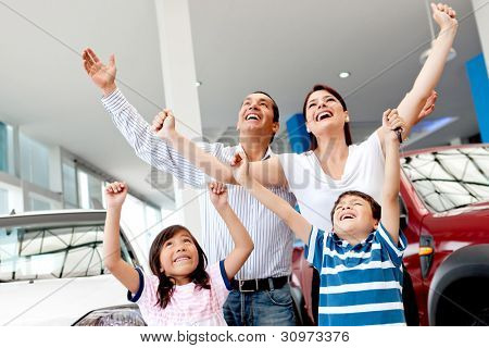 Excited family buying a car and celebrating with arms up