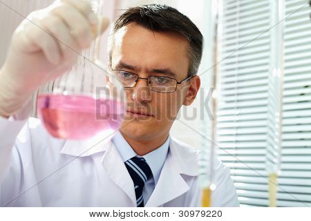Serious clinician gazing at flask with pink liquid in laboratory